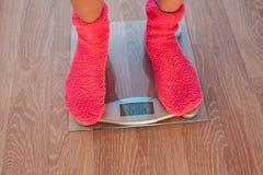 Το κορίτσι στις ρόδινες κάλτσες που στέκονται weigher Στοκ Εικόνα