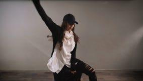 Το κορίτσι στον γκρίζο τοίχο στο στούντιο Ο χορός είναι διασκέδαση για την Χορός ως ευχαρίστηση παρά την ακριβή εμμονή απόθεμα βίντεο