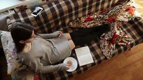 Το κορίτσι στον καναπέ με τον καφέ και το βιβλίο απόθεμα βίντεο
