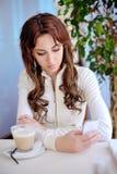 Το κορίτσι στον καφέ με το τηλέφωνο, γράφει sms Στοκ Εικόνες