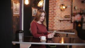 Το κορίτσι στον καφέ που περιμένει το φίλο της και χρησιμοποιεί ένα smartphone απόθεμα βίντεο