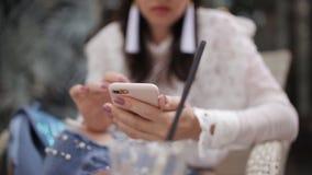 Το κορίτσι στον καφέ χρησιμοποιεί μια κινηματογράφηση σε πρώτο πλάνο smartphone φιλμ μικρού μήκους