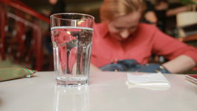 Το κορίτσι στον καφέ ψάχνει κάτι σε μια τσάντα σε ένα υπόβαθρο γυαλιού με το νερό απόθεμα βίντεο