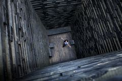 Το κορίτσι στον ξύλινο καλά Μοναξιά και απελπισία Παράξενη κατασκευή archetekturnoe στοκ φωτογραφία με δικαίωμα ελεύθερης χρήσης