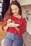 Το κορίτσι στο αρτοποιείο τρώει το επιδόρπιο Το όμορφο πρότυπο σε έναν καφέ τρώει τα γλυκά και το χαμόγελο Όμορφο κορίτσι σε ένα  στοκ εικόνες