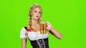Το κορίτσι στο βαυαρικό εθνικό κοστούμι πίνει την μπύρα και παρουσιάζει αντίχειρα πράσινη οθόνη απόθεμα βίντεο