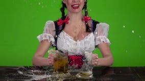 Το κορίτσι στο βαυαρικό κοστούμι σπάζει τα γυαλιά με την μπύρα πράσινη οθόνη κίνηση αργή απόθεμα βίντεο