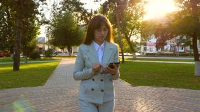 Το κορίτσι στο ελαφρύ κοστούμι πηγαίνει να εργαστεί με την ταμπλέτα διαθέσιμη Όμορφοι θηλυκοί περίπατοι επιχειρηματιών κατά μήκος απόθεμα βίντεο