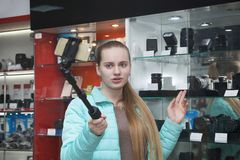 Το κορίτσι στο επαγγελματικό κατάστημα εξοπλισμού φωτογραφιών καταγράφει το βίντεο στο τηλέφωνο χρησιμοποιώντας selfie το ραβδί Σ στοκ φωτογραφία με δικαίωμα ελεύθερης χρήσης