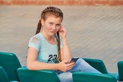 Το κορίτσι στο κάθισμα στις στάσεις Το κορίτσι αγαπά να ακούσει το τραγούδι στο τηλέφωνο Στοκ Εικόνα