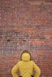 Το κορίτσι στο κίτρινο σακάκι που εξετάζει έναν τουβλότοιχο Στοκ φωτογραφίες με δικαίωμα ελεύθερης χρήσης