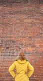 Το κορίτσι στο κίτρινο σακάκι που εξετάζει έναν τουβλότοιχο Στοκ Φωτογραφία