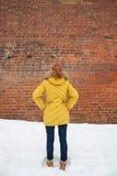 Το κορίτσι στο κίτρινο σακάκι που εξετάζει έναν τουβλότοιχο Στοκ Εικόνες