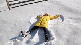 Το κορίτσι στο κίτρινο σακάκι Bringh βρίσκεται στο έδαφος και κάνει τον άγγελο χιονιού που έχει τη διασκέδαση κατά τη διάρκεια μι φιλμ μικρού μήκους