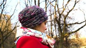 Το κορίτσι στο καπέλο, το μαντίλι λαιμών και ένα κόκκινο ντύνουν να καθίσουν σκεπτικά απόθεμα βίντεο
