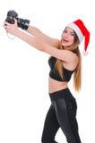 Το κορίτσι στο καπέλο Άγιου Βασίλη με μια κάμερα Χριστούγεννα φωτογράφων νέων κοριτσιών Χριστούγεννα selfie Στοκ φωτογραφίες με δικαίωμα ελεύθερης χρήσης