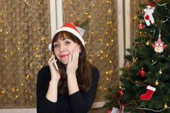 Το κορίτσι στο καπέλο Άγιου Βασίλη που μιλά στο τηλέφωνο Στοκ φωτογραφία με δικαίωμα ελεύθερης χρήσης