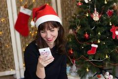 Το κορίτσι στο καπέλο Άγιου Βασίλη που μιλά στο τηλέφωνο Στοκ εικόνες με δικαίωμα ελεύθερης χρήσης