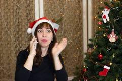 Το κορίτσι στο καπέλο Άγιου Βασίλη που μιλά στο τηλέφωνο Στοκ Εικόνες