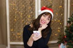 Το κορίτσι στο καπέλο Άγιου Βασίλη που μιλά στο τηλέφωνο Στοκ Εικόνα