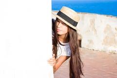 Το κορίτσι στο καπέλο αχύρου κρυφοκοιτάζει έξω από τον πίσω τοίχο Στοκ Εικόνα