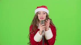 Το κορίτσι στο κοστούμι του βοηθού Santas τραγουδά σε ένα αναδρομικό μικρόφωνο και χορεύει με την ενεργητική μουσική πράσινη οθόν απόθεμα βίντεο