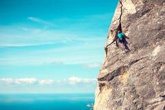 Το κορίτσι στο κράνος αναρριχείται στο βράχο Στοκ εικόνα με δικαίωμα ελεύθερης χρήσης