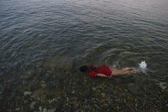 Το κορίτσι στο κόκκινο λούζει στα σαφή νερά της θάλασσας Στοκ Εικόνα