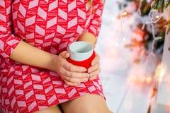 Το κορίτσι στο κόκκινο φόρεμα κρατά ένα φλιτζάνι του καφέ, κινηματογράφηση σε πρώτο πλάνο Στοκ Εικόνα