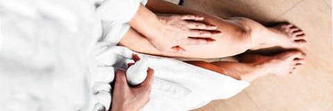 Το κορίτσι στο λουτρό βάζει την αντι -αντι-cellulite κρέμα, τον ορό στα πόδια και το σώμα απομονωμένη έννοια λευκή γυναίκα προσοχ στοκ εικόνες