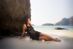 Το κορίτσι στο μαύρο διαφανές φόρεμα βρίσκεται στην άμμο Στοκ Εικόνες