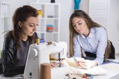 Το κορίτσι στο Μαύρο ράβει Ο συνάδελφός της εξετάζει τις σημειώσεις Στοκ Εικόνες