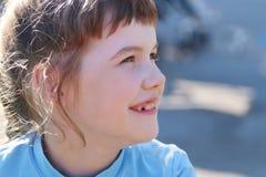 Το κορίτσι στο μπλε κοιτάζει μακριά και χαμογελά στη θερινή ηλιόλουστη ημέρα Στοκ Εικόνα
