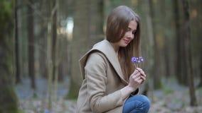 Το κορίτσι στο πάρκο που θαυμάζει τα snowdrops φιλμ μικρού μήκους