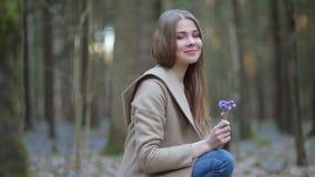 Το κορίτσι στο πάρκο που θαυμάζει τα snowdrops απόθεμα βίντεο