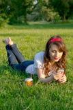 Το κορίτσι στο πάρκο που φορά τα ακουστικά με το κινητό τηλέφωνο και ένα φλυτζάνι Στοκ Φωτογραφία