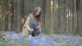 Το κορίτσι στο πάρκο συλλέγει snowdrops φιλμ μικρού μήκους