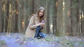 Το κορίτσι στο πάρκο συλλέγει snowdrops απόθεμα βίντεο