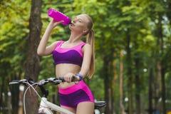Το κορίτσι στο ποδήλατο σταμάτησε και πόσιμο νερό από το μπουκάλι Στοκ φωτογραφία με δικαίωμα ελεύθερης χρήσης