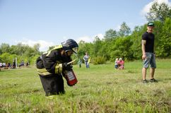 Το κορίτσι στο πυροσβέστη ομοιόμορφο προετοιμάζεται εξαφανίζει την καίγοντας ρόδα στην κατάρτιση στοκ φωτογραφίες