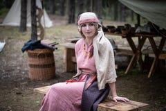 Το κορίτσι στο σλαβικό κοστούμι της ηλικίας Βίκινγκ κάθεται σε έναν ξύλινο πάγκο στοκ εικόνες