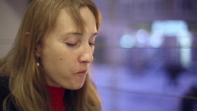 Το κορίτσι στο τσάι κατανάλωσης καφέδων και κατανάλωση ενός κουλουριού απόθεμα βίντεο