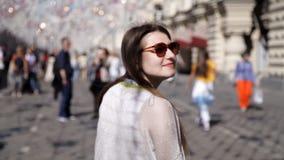 Το κορίτσι στο υπόβαθρο των φωτεινών σηματοδοτών στο καλώδιο Οι λαμπτήρας-λαμπτήρες κρεμούν τις διακοσμήσεις ενάντια στο μπλε ουρ απόθεμα βίντεο