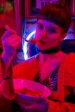 Το κορίτσι στο φραγμό νέου έχει τη διασκέδαση Στοκ Φωτογραφίες