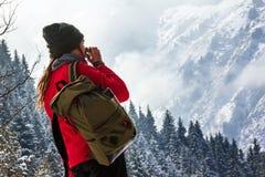 Το κορίτσι στο χειμερινό δασικό Α κορίτσι πίνει τον καφέ και εξετάζει το τοπίο Στοκ Φωτογραφίες