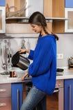 Το κορίτσι στο χύνοντας τσάι κουζινών Στοκ Φωτογραφία