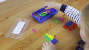 Το κορίτσι συλλέγει τις γεωμετρικές μορφές φιλμ μικρού μήκους