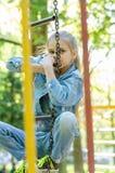 Το κορίτσι συλλογίστηκε αναρριχημένος στην κρεμώντας σκάλα στην παιδική χαρά στοκ εικόνες