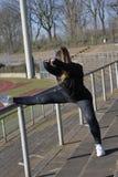 Το κορίτσι συμμετέχει στον αθλητισμό στο στάδιο στοκ φωτογραφία