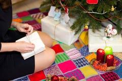 Το κορίτσι συσκευάζει τα δώρα κοντά σε ένα χριστουγεννιάτικο δέντρο Στοκ εικόνα με δικαίωμα ελεύθερης χρήσης